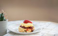 Traditional English Scones with strawberry jam and clotted cream topped with fresh strawberry Royalty Free Stock Photo