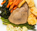 Traditional english sunday lunch british of roast beef roasted potatoes carrots parsnips kale cauliflower on china plate Royalty Free Stock Images