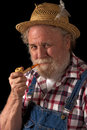 Traditional farmer with straw hat and corncob pipe Royalty Free Stock Image