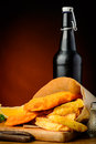 Traditional fish and chips and beer wrapped in paper bottle Stock Image
