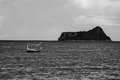 Traditional fishing boat laying alone on the sea with island in background ,selective focus,black and white color picture style Royalty Free Stock Photo