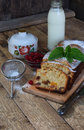 Traditional fruitcake with raisins, dried apricots, cherry for Christmas on wooden background. Sliced freshly baked cake and milk. Royalty Free Stock Photo