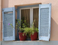 Traditional greek blue window shutters and flowers with white frames in pots Stock Image