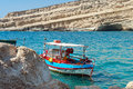 Traditional greek fishing boat stays parked near beach of Matala town on Crete island, Greece Royalty Free Stock Photo