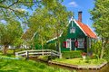 Traditional green dutch house with little wooden bridge against blue sky in the Zaanse Schans village, Netherlands. Famous tourism Royalty Free Stock Photo