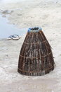 Traditional handmade fishing trap and flip flops on sand a brazilian cage made of sticks twine this is used in rivers lakes here Stock Images
