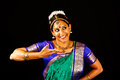 Traditional indian dance expression young woman in sari dancing classical bharatanatyam on a black background Royalty Free Stock Image
