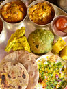 Traditional indian vegeterian platter consisting of different curries roti and sweet Stock Images