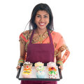 Traditional indian woman baking bread and cupcakes in sari wearing apron holding tray isolated on white Royalty Free Stock Photos