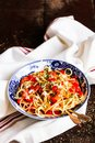 Traditional italian food. Bowl of homemade pasta spaghetti with fried shrimps or prawns, roasted red bell pepper, salted crumbled Royalty Free Stock Photo