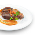 Traditional italian osso buco meat served with vegetables and parsley on white Royalty Free Stock Photography