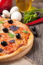 Traditional italian pizza margherita with tomatoes olives and basil on vintage rustic background Stock Photo