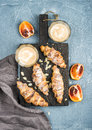 Traditional Italian style home breakfast. Latte in glasses, almond croissants and red bloody Sicilian oranges over Royalty Free Stock Photo