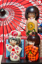 Traditional japanese wooden kokeshi dolls and wagasa umbrella in background touristic souvenir Stock Image