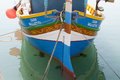 Traditional luzzu boats malta a is a fishing boat from the maltese islands they are brightly painted in shades of yellow red green Royalty Free Stock Photo