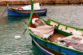 Traditional maltese boat in a popular and quaint harbor village in malta Stock Image