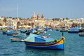 Traditional maltese luzzu fishing boats in marsaxlokk harbor mediterranean island of malta march Royalty Free Stock Images