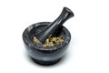 Traditional mortar and pestle with herbs a marble used for grinding up or drugs usually used for cooking or by apothecaries shot Stock Images