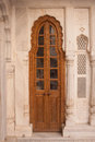 Traditional narrow brown wooden door with ornate stone doorframe exploring the delights of junagarh fort bikaner Stock Photos