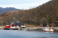 Traditional norwegian village small with red wooden houses and small fishing boat nearby Stock Photos