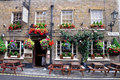 Traditional old english pub external detail decorated with flowers in tubs and hanging baskets Royalty Free Stock Images