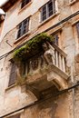 Facade of an old house with a stone balcony decorated with lion heads Royalty Free Stock Photo