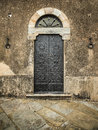 Traditional old vintage iron door in tuscany italy and grunge wall europe Stock Photo