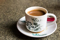 Traditional oriental Chinese coffee in vintage mug and saucer in soft focus setting with ambient light Royalty Free Stock Photo