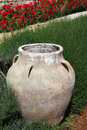 Traditional ornamental jar amid green grass red flowers Royalty Free Stock Photography