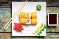 Traditional philadelphia sushi rolls on white plate with chopstick and wasabi top view Stock Photos