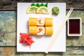 Traditional philadelphia sushi rolls on white plate with chopstick and wasabi top view Royalty Free Stock Photos