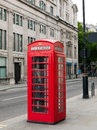 Traditional phone booth in london characteristic red a street uk Royalty Free Stock Photo