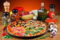 Traditional pizza and ingredients still life with quattro stagioni Royalty Free Stock Photo