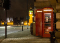 Traditional red phone booth in london with the big ben in the ba background at night Royalty Free Stock Images