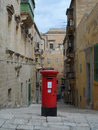 Traditional red post box in narrow street in malta typical scene valletta of an old fashioned british standing at the top of steps Stock Photography