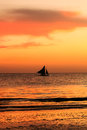 Traditional sailing boat in silhouette with a tropical sunset Royalty Free Stock Photo