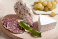 Traditional salami cheese brie, grapes, basil Stock Images