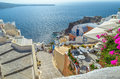 Traditional santorini s rocky architecture with beautiful view on caldera oia greece august steps down to the sea and Royalty Free Stock Images