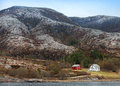 Traditional small norwegian village with red and white wooden houses on rocky coast Stock Photography