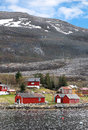 Traditional small norwegian village with red wooden houses on rocky coast with mountains on the horizon Stock Photos