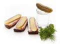 Traditional snack of rye bread pickles bacon and vodka decorated with bunch of parsley and dill Stock Image