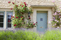 Traditional stone house with blue doors, red roses, flowering lavender Royalty Free Stock Photo
