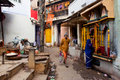 Traditional street life with a sellers a praying woman and passers by people varanasi india at morning varanasi urban Royalty Free Stock Photos