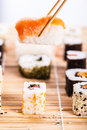 Traditional sushi bar a salmon nigiri being picked up with chopsticks with different types of maki pieces on a wooden mat in the Royalty Free Stock Photo
