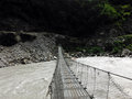 Traditional Suspension Bridge Crossing a Wild River Royalty Free Stock Photo