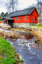 Traditional swedish watermill with small river vertical view of old water mill Royalty Free Stock Images