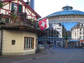 Traditional swiss house with flag near a shopping mall made of glass window Stock Photography