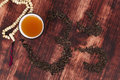 Traditional tea drinking cup of dry leaves forming ohm symbol and buddhist necklace Stock Image