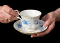 Traditional teacup and saucer held in English lady`s hands.