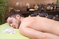 Traditional thai massage - man getting hotstone treatment Stock Images
